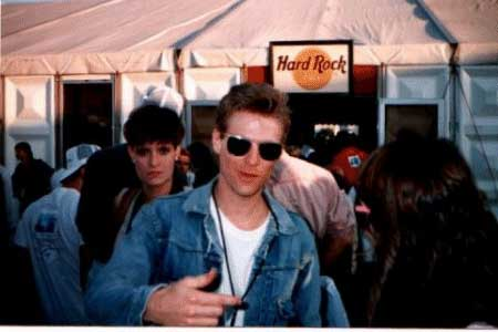 "Bryan Adams backstage at the Hard Rock Tent. This was taken before the show, where many of the band members and special guests were wondering around and having a few cold ones at the Hard Rock. Tom's passes didn't give them clearance to get in, so they hung outside. The woman glaring over his shoulder is understood to be Bryan's manager. She apparently wasn't too happy that Bryan was actually MINGLING with the fans! Tom said that Bryan was ""very cool"" and in his opinion "" a highlight of the concert""."