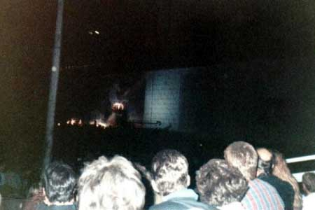 """Taken during """"The Trial,"""" you can see Albert Finney at center stage on a raised platform playing the Judge. Also at this point The Wall itself became a giant movie screen, with the Gerald Scarfe animation from """"The Wall"""" movie playing on both sides of center stage. What was truly amazing about this (Tom said it doesn't really come across in the pics) was the stunning clarity of all the images projected onto the Wall through out the evening. They were brilliantly lit, and crystal clear."""