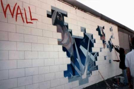 """The one that interested Tom & Carin the most, was the gentleman who was still in the process of painting the foldout art from """"The Wall"""" album onto the Berlin wall! He had started it when he heard about the concert coming, and while he didn't have a ticket, still wanted to paint the picture as a tribute to the show! The tour bus wasn't supposed to even stop there, but those on the bus made the driver stop so they could get pics! While originally schedualed to be torn down, Tom & Carin were told that the government was reconsidering leaving these sections up as a tourist atraction, so if you ever visit Berlin these pics may still be there. Tom hopes so!"""