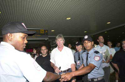 A nervous looking Roger is ushered through the airport by security guards